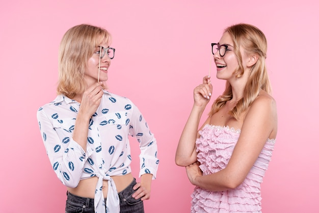 Young women with glasses mask looking at each other