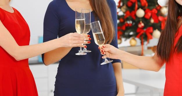 オフィスでクリスマスを祝うシャンパングラスを持つ若い女性、クローズアップ