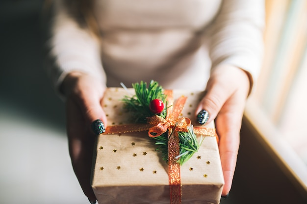 Young women with glitter nails holding christmas present box