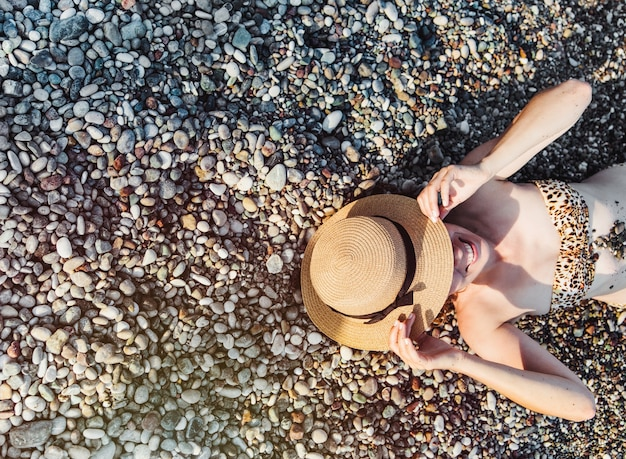 Young women with a hat laying down on the beach top view