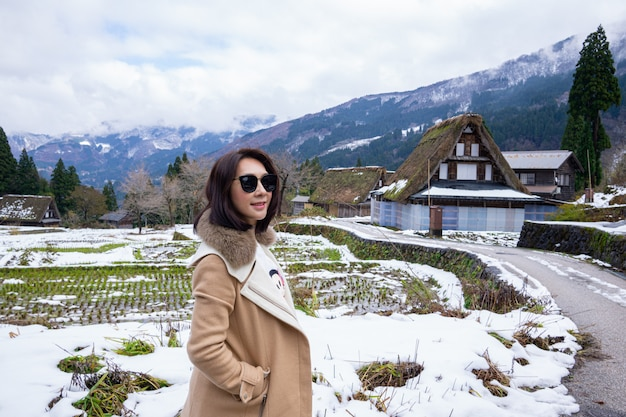 Young women with heritage wooden farmhouse village surrounded in japan