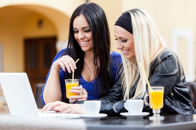 Молодые женщины с ноутбуком и пить сок