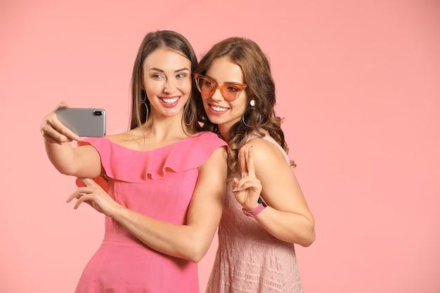 Молодые женщины с мобильным телефоном, делающие селфи на розовом