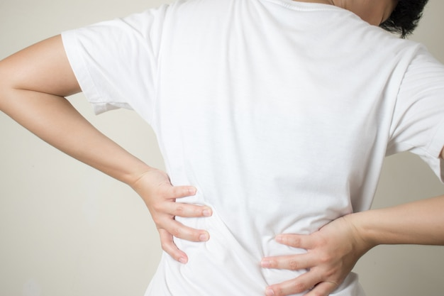 Young women with muscular pain in her back, caused by heavy lifting, spinal diseases.