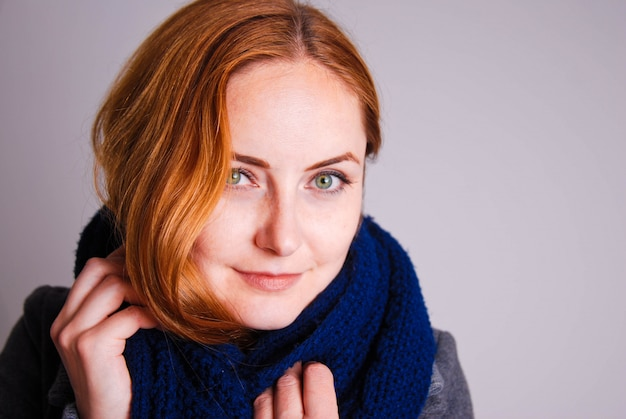 Young women with red hair and blue knitted scarf.