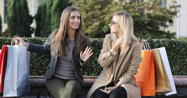 Молодые женщины с сумками сидят на скамейке в парке
