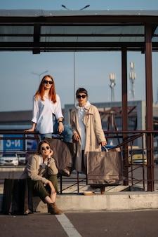 Молодые женщины с сумками на автобусной остановке