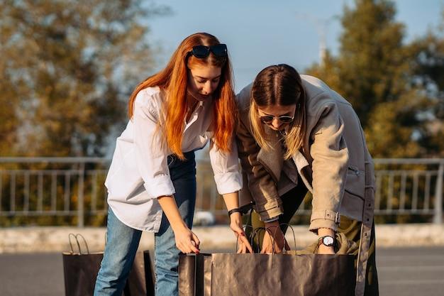 Молодые женщины с хозяйственными сумками на парковке