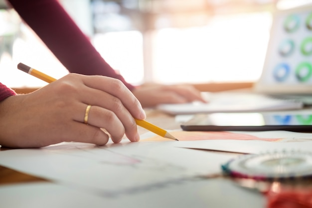 ファッションデザイナーとして働く若い女性たちが、職場のスタジオでアトリエ紙で服のスケッチを描く。