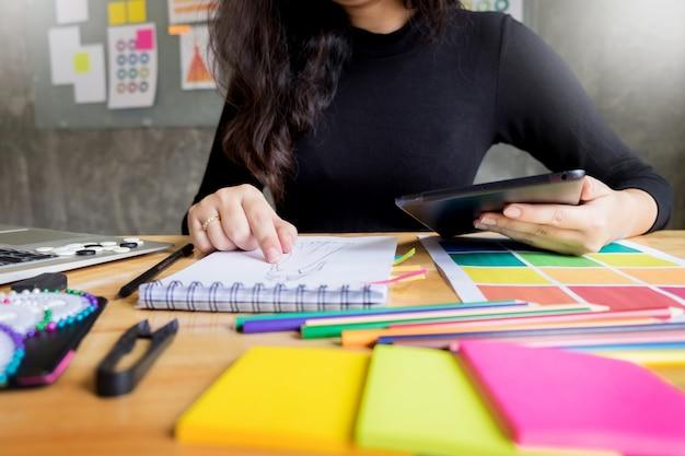 ファッションデザイナーとして働く若い女性たちが衣服のスケッチを描く