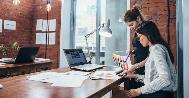 현대 사무실에서 책상에 앉아 색상 견본 및 스케치를 사용하여 새로운 웹 디자인을 작업하는 젊은 여성.