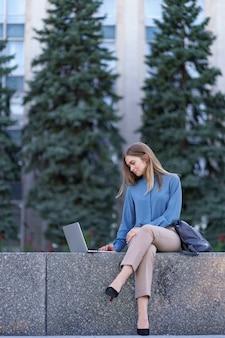 都市広場のラップトップに取り組んでいる若い女性