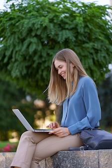 Молодые женщины, работающие на ноутбуке на городской площади