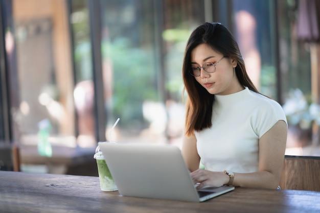カフェ、ビジネスコンセプトの木製テーブルでノートパソコンで作業する若い女性