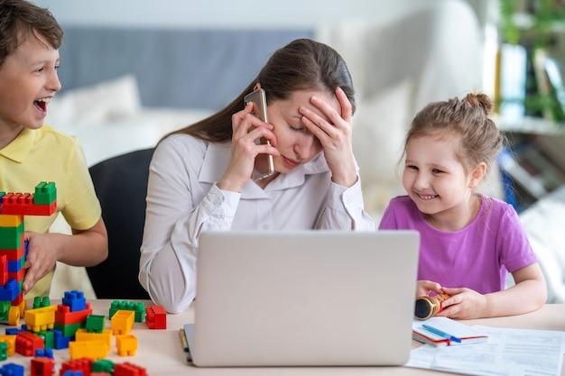 Молодые женщины работают дома с ноутбуком вместе с детьми. дети шумят