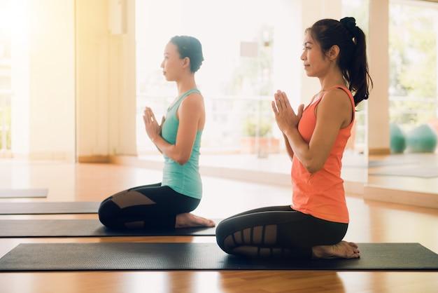 실내의 젊은 여성 요가는 내면의 평화를 탐험하기 위해 요가를 연습하면서 침착하고 명상을 유지합니다. 요가와 명상은 건강에 좋은 이점이 있습니다. 요가 스포츠와 건강한 라이프 스타일을위한 사진 개념