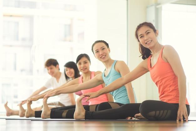 Молодые женщины йоги в помещении сохраняют спокойствие и медитируют, практикуя йогу