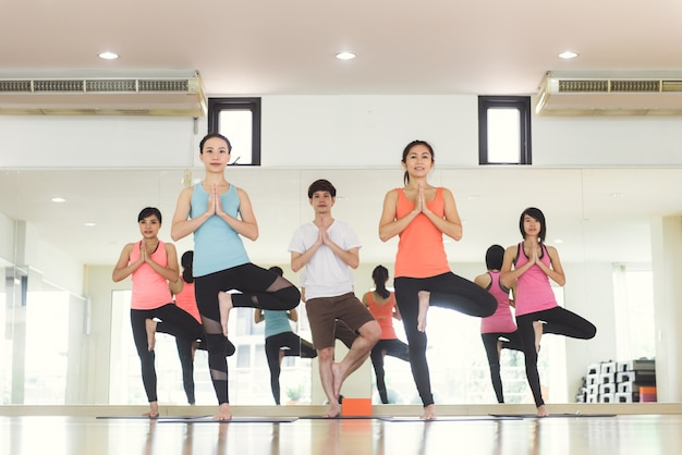 Le donne giovani yoga all'interno mantengono la calma e meditano mentre praticano lo yoga per esplorare la pace interiore. yoga e meditazione hanno buoni benefici per la salute. concetto fotografico per yoga sport e stile di vita sano