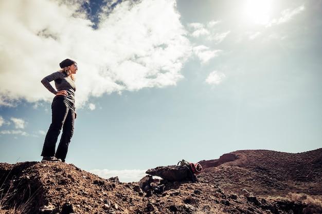山のトレッキング中に立って道路を見ている若い女性のハイカー-観光と冒険旅行のライフスタイルの概念-アウトドアレジャー活動を楽しんでいる健康な人々-中年の女性とn