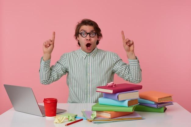 Молодой изумленный студент в очках сидит за столом с ноутбуком, смотрит в камеру с широко открытым ртом и хочет привлечь ваше внимание к копирую над головой, изолированному на розовом фоне.