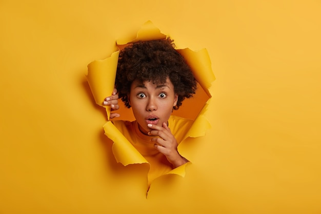 Young wondered young woman with afro hairstyle, opens mouth, stands in ripped paper hole background