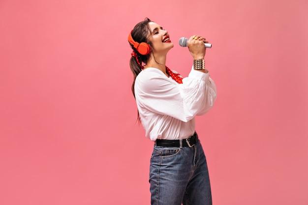 Молодая замечательная женщина в хорошем настроении поет в микрофон и слушает музыку в наушниках на розовом изолированном фоне.