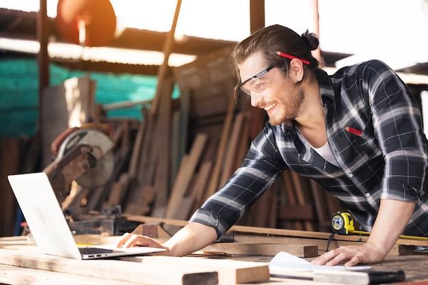 노트북으로 온라인으로 작업하는 목공 장비로 가득한 그의 큰 작업장에서 작업대에 기대어 수염을 가진 젊은 목공예가