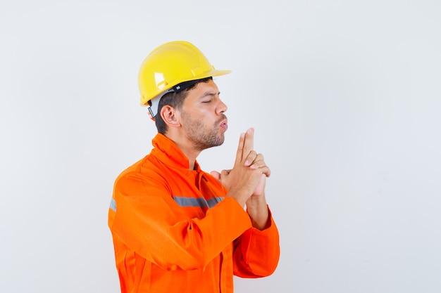 Giovane operaio che soffia sulla pistola fatta da mani in uniforme, casco e guardando fiducioso.