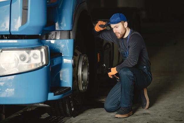 Un giovane operaio controlla la ruota. malfunzionamento del camion. lavoro di servizio.