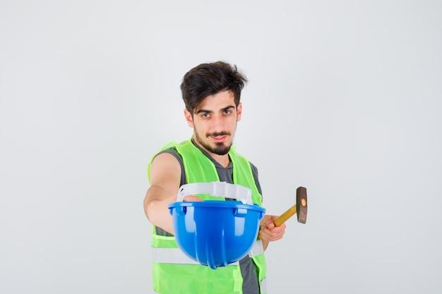 Giovane operaio in uniforme da costruzione che tiene in mano cappello e ascia e sembra amabile