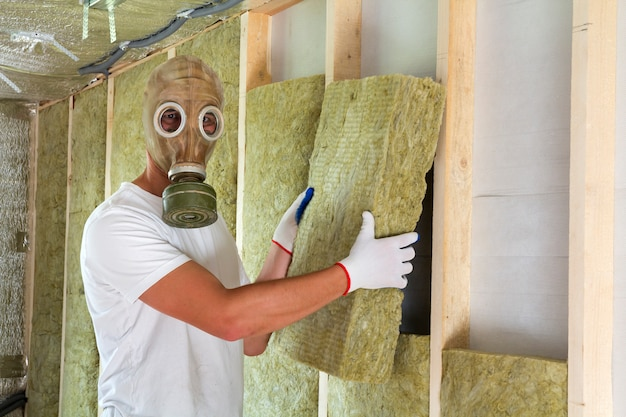 Young worker in gas mask insulating rock wool insulation staff in wooden frame for future house walls for cold and heat barrier.
