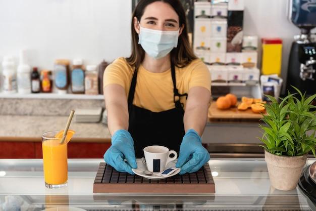 顔の保護マスクを着用しながらレストラン内でコーヒーを与える若い労働者