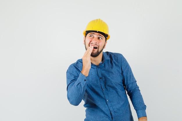 Giovane operaio che ha mal di denti doloroso in camicia, casco e che sembra a disagio