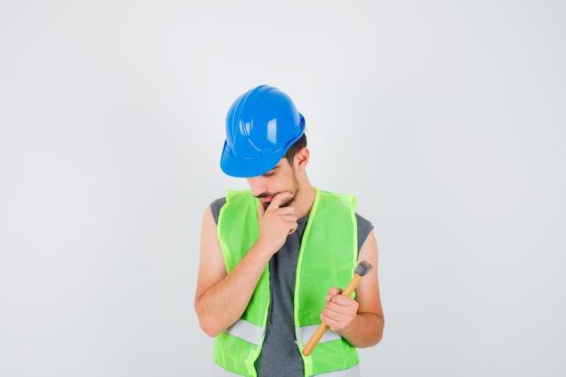 Молодой рабочий держит топор в одной руке и стоит в позе мышления в строительной форме и выглядит задумчиво