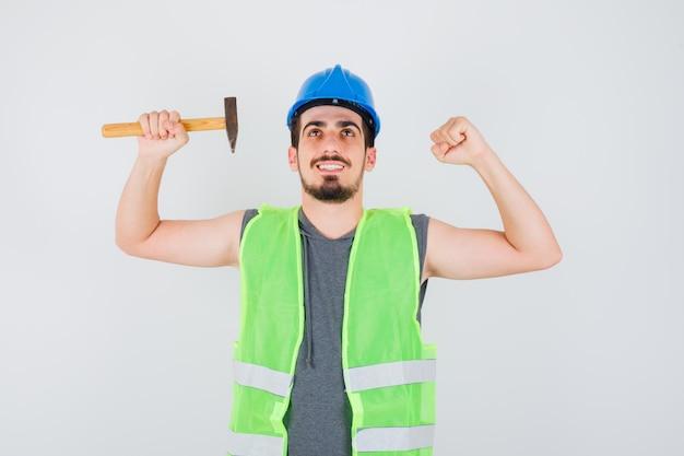 Молодой рабочий держит топор в одной руке, показывая жест в строительной форме и выглядит счастливым