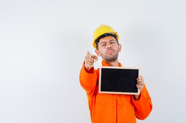 Lavagna della holding del giovane operaio, che indica davanti in uniforme, casco.