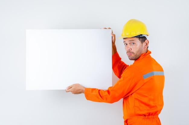 Giovane operaio che tiene tela bianca in uniforme, vista posteriore del casco.