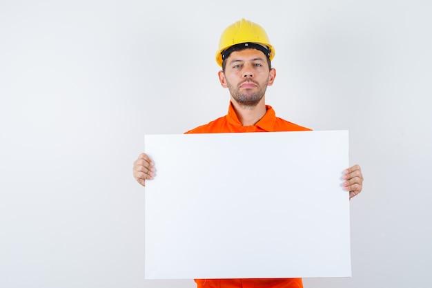 Giovane operaio che tiene tela bianca in uniforme, casco e che sembra fiducioso.