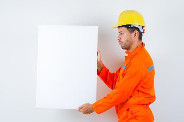 Giovane operaio che tiene tela bianca in uniforme, casco.