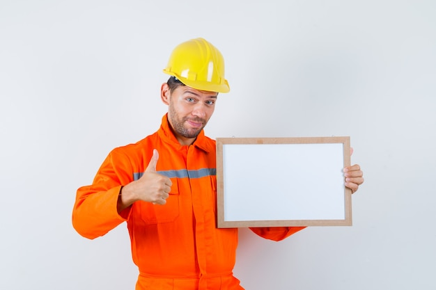 Young worker holding blank frame, showing thumb up in uniform, helmet and looking glad.