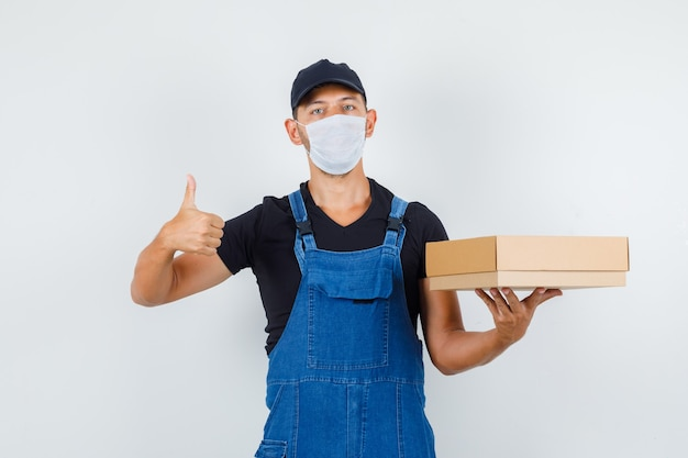 Young worker holding cardboard box with thumb up in uniform, mask front view.