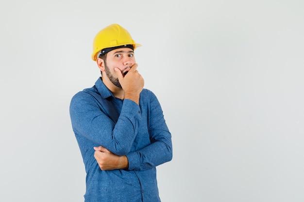 젊은 노동자 셔츠, 헬멧에 열린 입에 손을 잡고 놀란 찾고