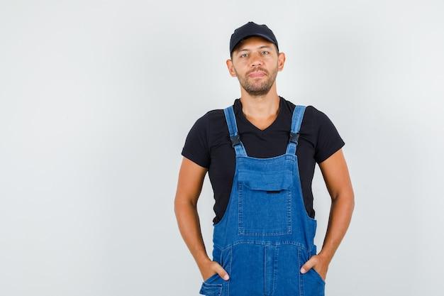 젊은 노동자 유니폼 주머니에 손을 잡고 쾌활한, 전면보기를 찾고.