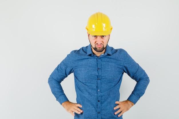 Giovane operaio che tiene le mani sulla vita in camicia, casco e che sembra furioso