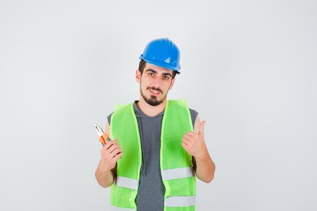 ペンチを持って、建設の制服を着て親指を上げて幸せそうに見える若い労働者