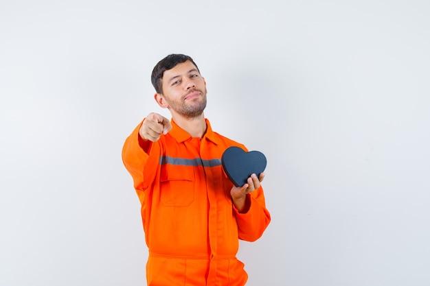 Молодой работник держит подарочную коробку, указывая на фронт в униформе и выглядит уверенно.