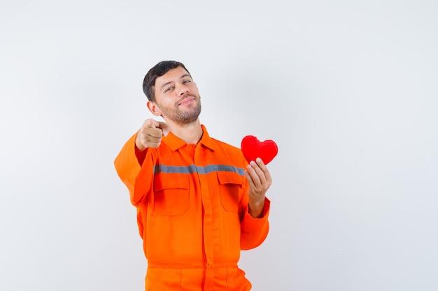 Giovane operaio che tiene cuore rosso, che indica davanti in uniforme e che sembra allegro.