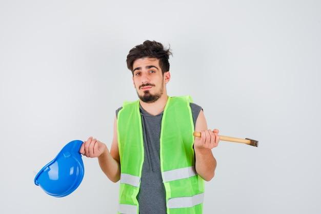 Молодой рабочий в строительной форме держит топор в одной руке и кепку в другой и выглядит озадаченным
