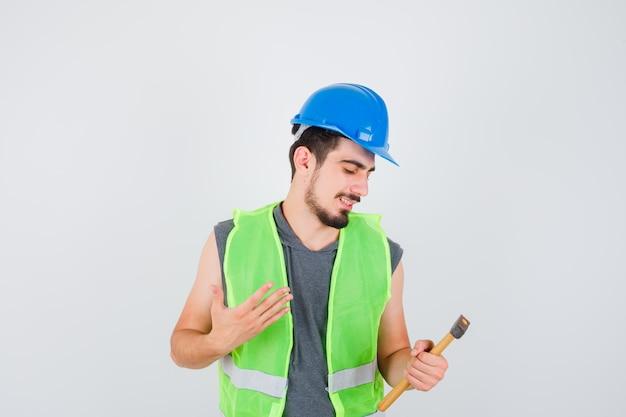 Молодой рабочий в строительной форме держит топор в одной руке, смотрит на него и выглядит счастливым