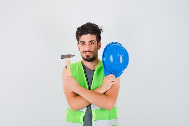 Молодой рабочий в строительной форме держит топор в одной руке, снимает кепку и выглядит счастливым